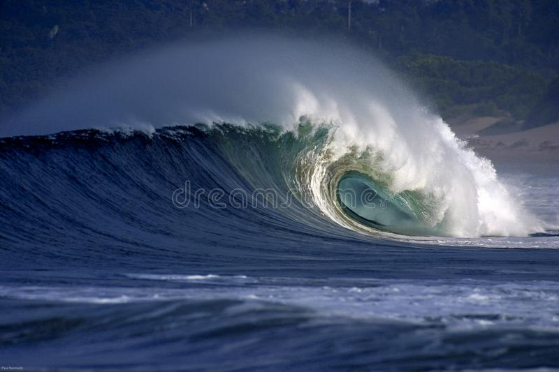 Large blue surfing wave breaking on sand beach royalty free stock photo