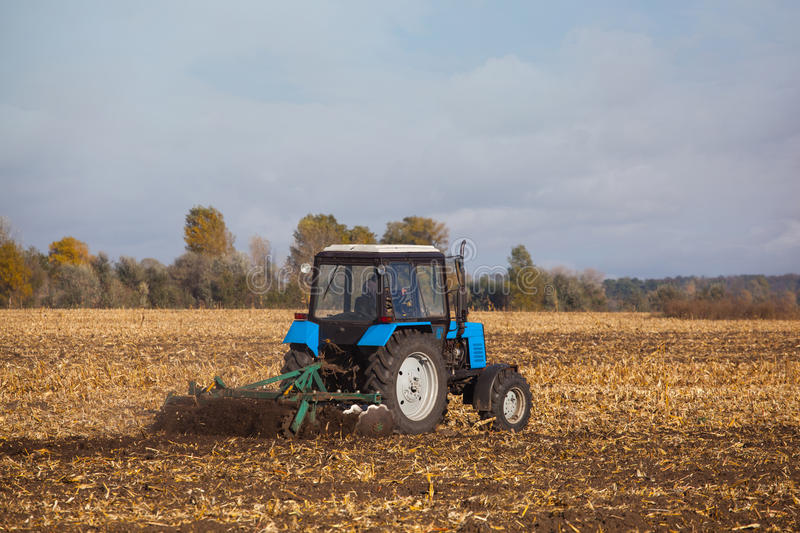 Large blue tractor plow plowed land after harvesting the maize crop on a sunny, clear, autumn day. royalty free stock photography