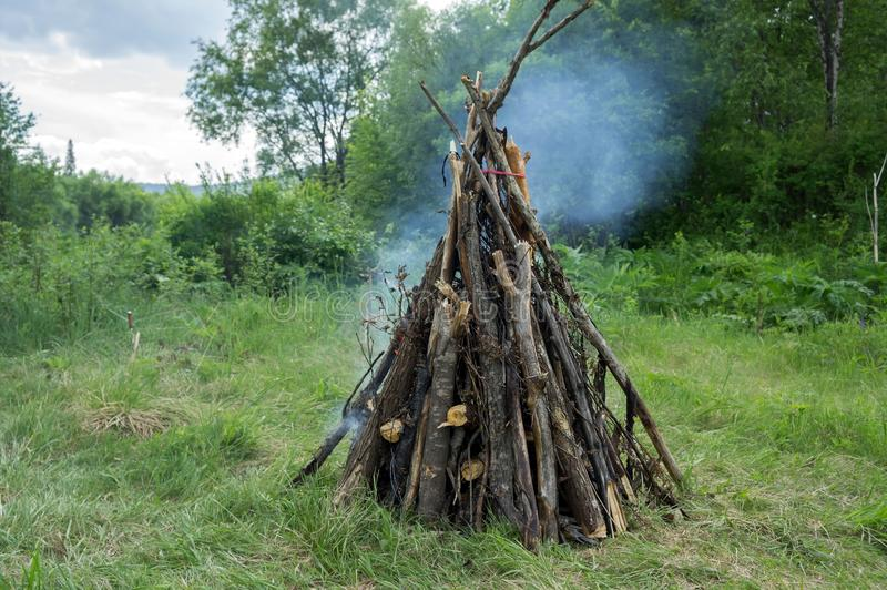 Large bonfire from a dry cripple burns in the forest, against the background of trees. Summer landscape. Large bonfire from a dry cripple burns in the forest stock photo