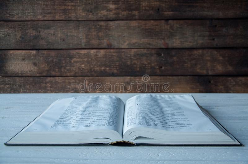The big book of the Bible lies on a wooden table. In the dark. A light shines on the book from above. stock image