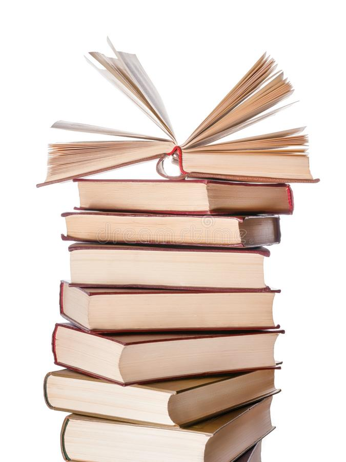 Large books pile with single open book isolated stock photo