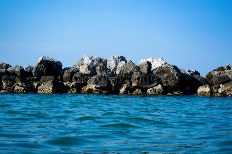 Large boulders in the sea against the blue sky royalty free stock image