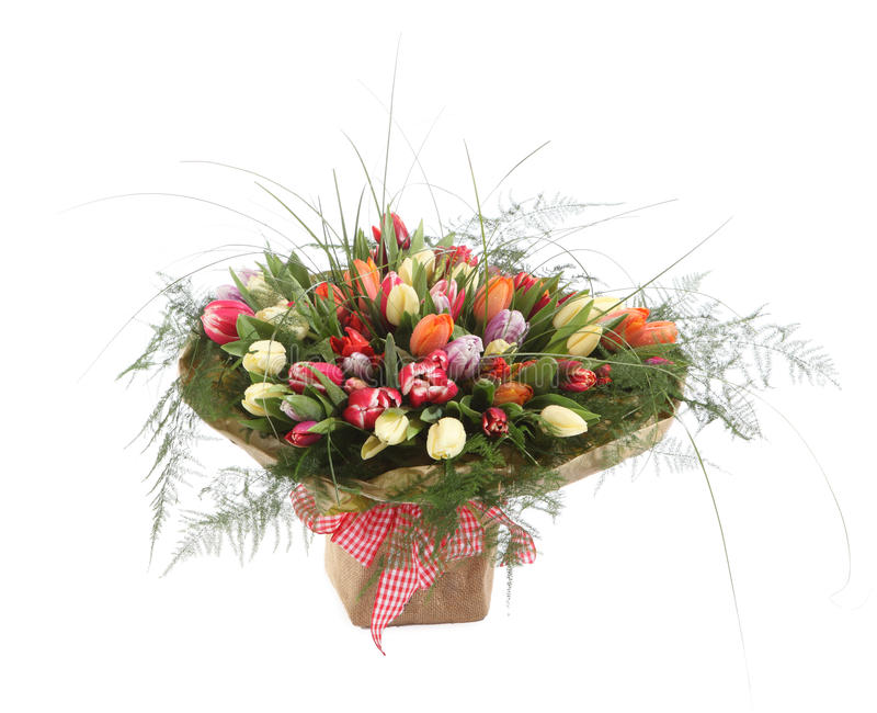 A large bouquet of color tulips in a square vase. Square floral arrangement of tulips of different colors. A large bouquet of color tulips in a square vase. The stock images