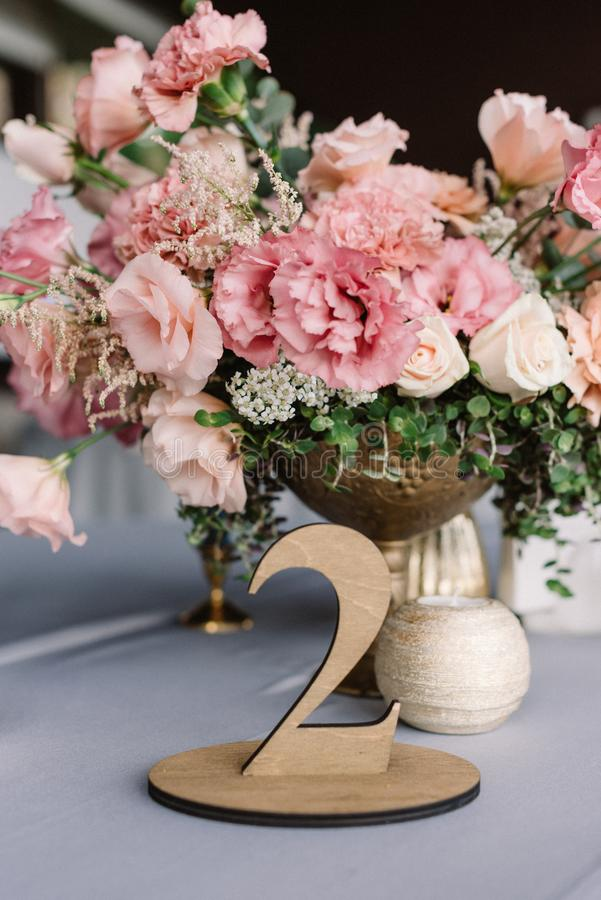 A large bouquet of pink flowers and a stylish elegant wood table room. Elegant decor of a modern European wedding in a restaurant stock photos