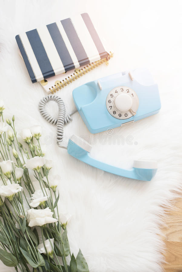 A large bouquet white flowers, notebooks and blue retro phone on wood floor on a white fur carpet. Cozy, fashion comfortable femin stock photography