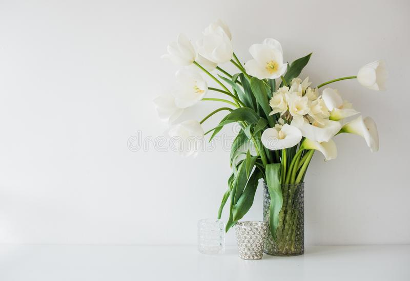 Large bouquet of white spring flowers in a vase, daffodils, tuli. Ps and feces in home interior decor royalty free stock photos