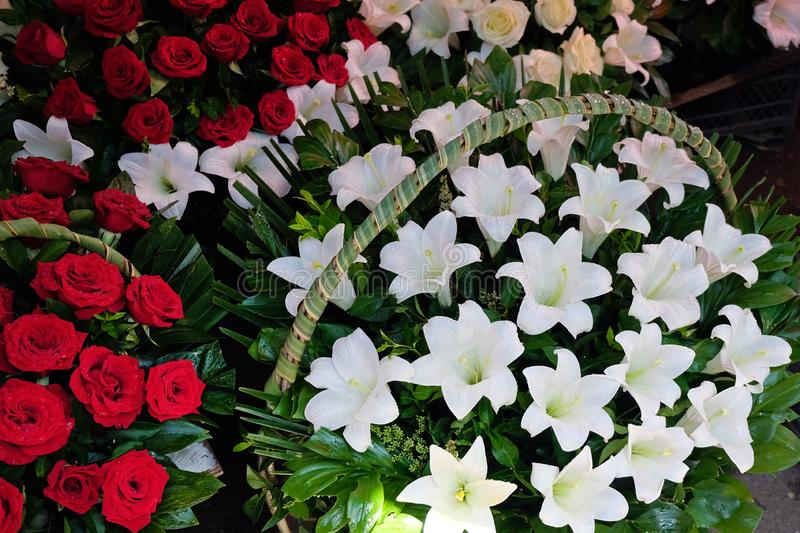 Large bouquets of red roses and large baskets with white lilies. Sale of flowers in the center of Tbilisi at the flower market. Romantic gifts for loved ones stock photography