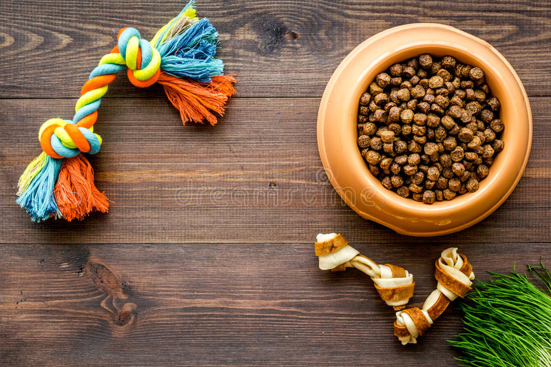 Large bowl of pet - dog food with toys on wooden background top view mockup. Large plastic bowl of pet - dog food with toys on wooden table background top view royalty free stock images