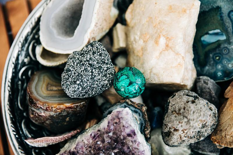 Large bowl of specialty rocks and crystals. In various colors sitting on a wood-slatted table modern home decor decoration stock image