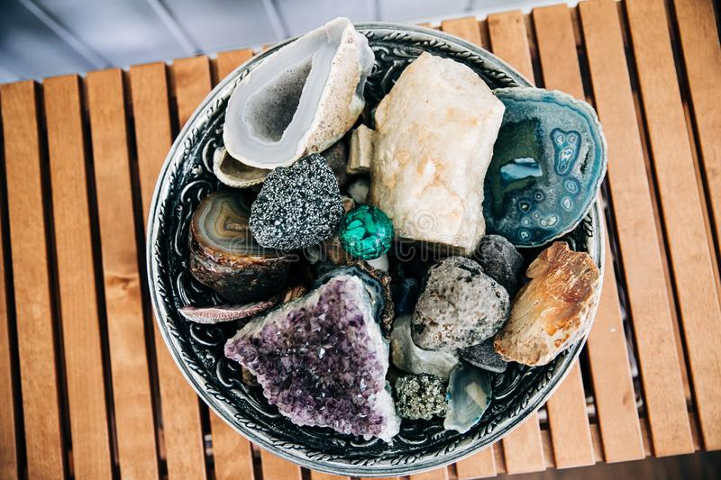 Large bowl of specialty rocks and crystals. In various colors sitting on a wood-slatted table modern home decor decoration stock images