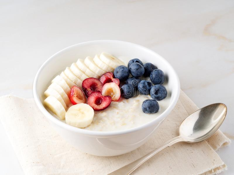 Large bowl of tasty and healthy oatmeal with fruits and berry for Breakfast, morning meal. Side view, white marble table stock photo