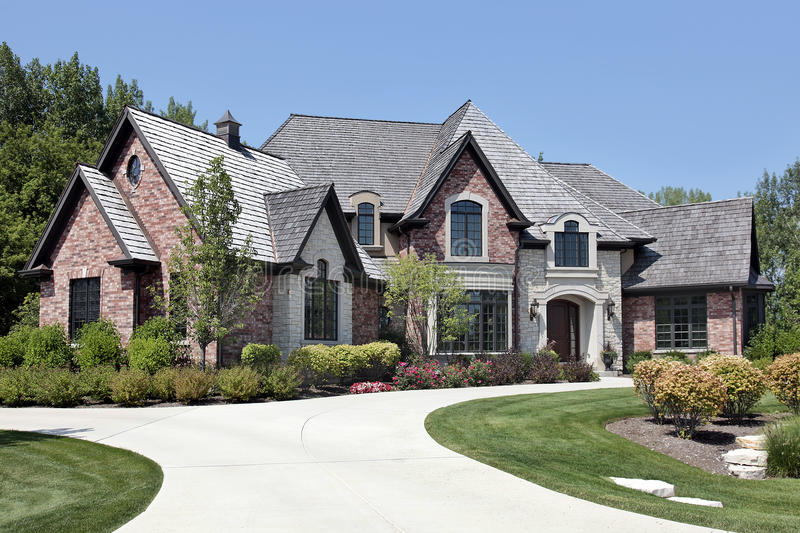 Large brick home with circular driveway stock images