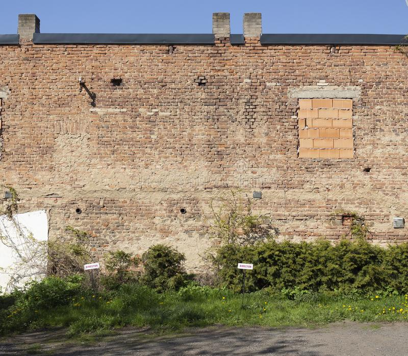Large old brick wall with blind window and two directors parking signs stock photo