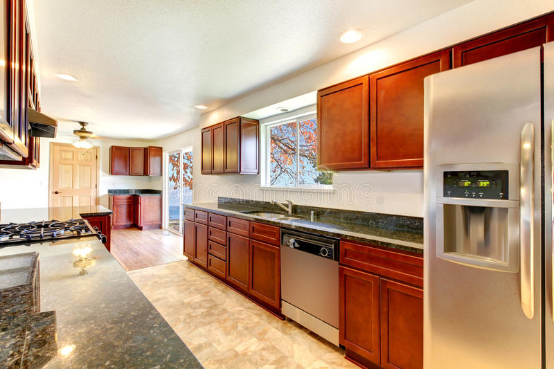 Large bright kitchen with dark cherry cabinets. royalty free stock photography
