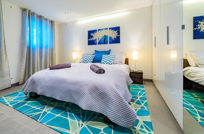 Bright luxury modern bedroom in decorated in blue and green stock image