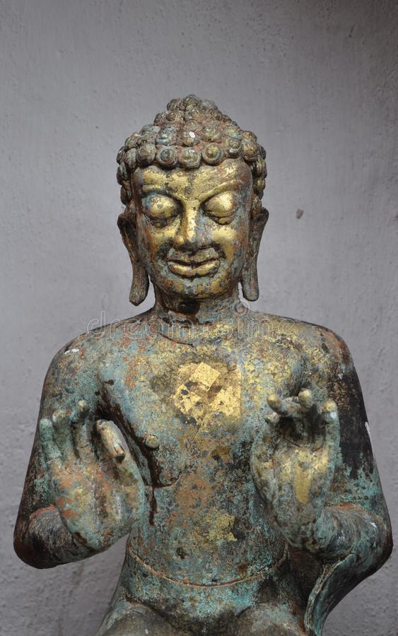 Large bronze buddha statue with vitarka Mudra hand gesture. Copper buddha statue showing Vitarka Mudra hand gesture, which symbolises reason, teaching and giving royalty free stock photos