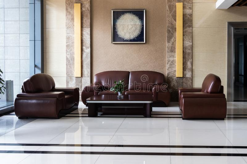 Large brown leather sofas in the room around the glass table. Business office for negotiations, marble floor. Large brown leather sofas in the room around the stock images