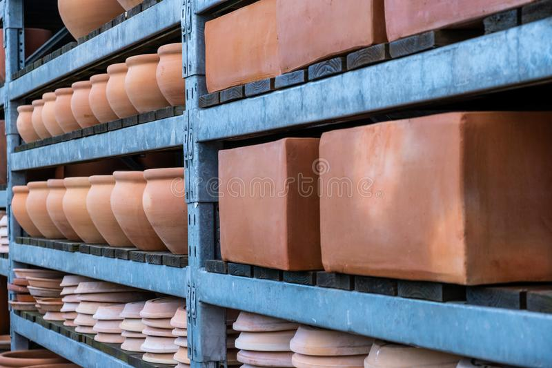 Terracotta flower pots on metal shelves. Large brown terracotta flower pots on metal shelves royalty free stock photos