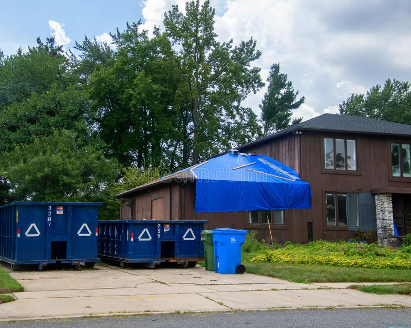 Large brown wooden house is seen with blue tarp over garage roof and two dumpsters in the driveway stock photography