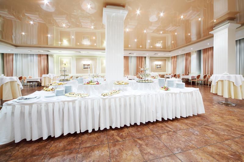 Large buffet and small round tables with tablecloths royalty free stock photo
