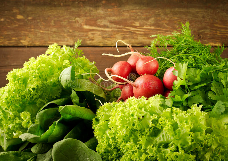 Large bunch of fresh Organic vegetables, radish, spinach, salad and greens on old wooden table, closeup. Dark rustic style stock photos