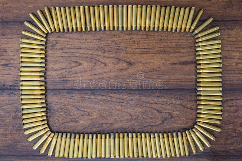 Large caliber bullets rectangle background. Large caliber bullets rectangle with wood background royalty free stock photography