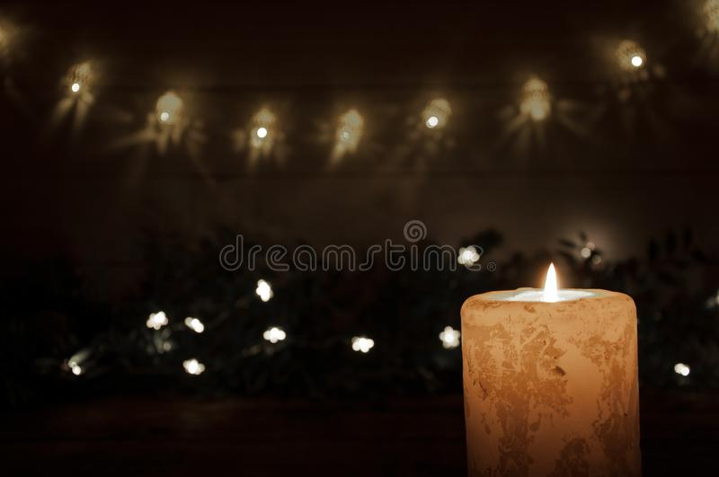 A large candle burns in the dark on a black background. Garland lights and stars. Christmas and New Year. A large candle burns in the dark on a black background royalty free stock images