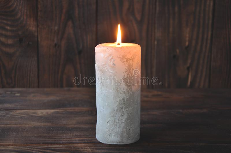 A large candle burns in the darkness on a wooden texture background stock image