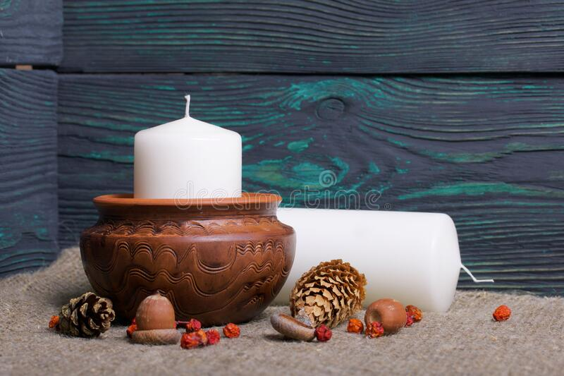 A large candle in a clay vessel. Acorns, rowan berries are scattered nearby and a candle lies. Against the background of brushed. Boards royalty free stock image