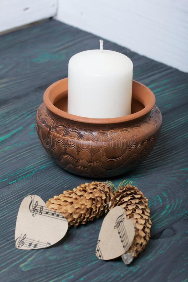 A large candle in a clay vessel. Decorated with cones and hearts cut out of paper. It stands on painted boards painted in black. And green stock image