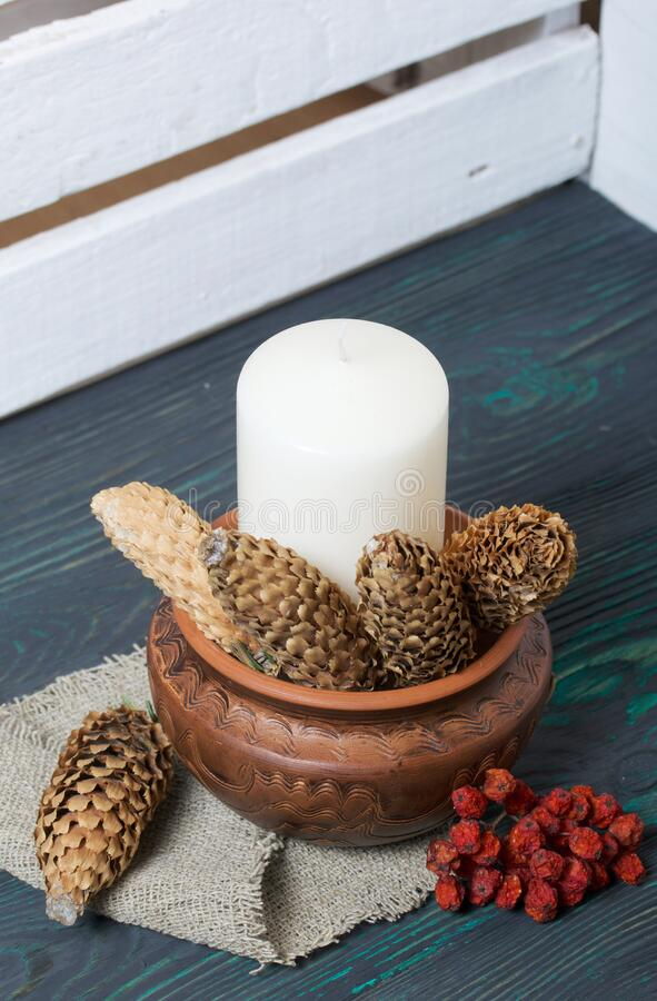 A large candle in a clay vessel. Decorated with fir cones and mountain ash. It stands on painted boards painted in black and green.  stock images
