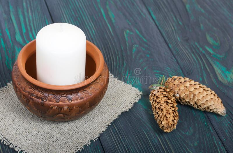 A large candle in a clay vessel. Decorated with fir cones. It stands on painted boards painted in black and green.  stock photography