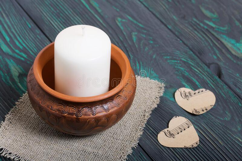 A large candle in a clay vessel. Decorated with hearts cut out of paper. It stands on painted boards painted in black and green.  royalty free stock images