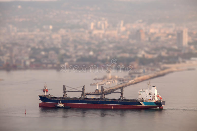 Large cargo ship arriving in port. Tilt-shift effect royalty free stock photography