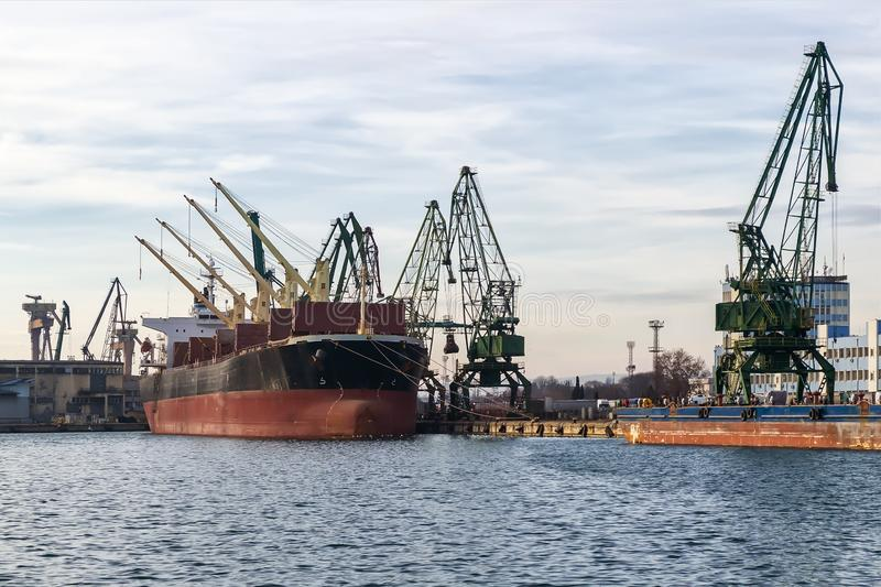 Large cargo ship in the seaport during loading. Cranes load the cargo into the ship. The work of the seaport. Industrial seascape. On a daytime royalty free stock image