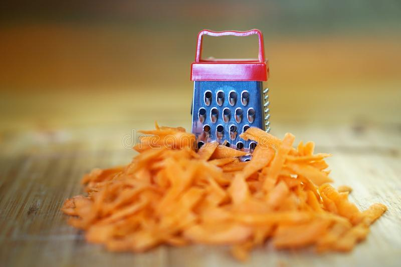 A large carrot and a small grater on a cutting board in the kitchen. Optical illusion. Close-up. Shallow depth of field stock images