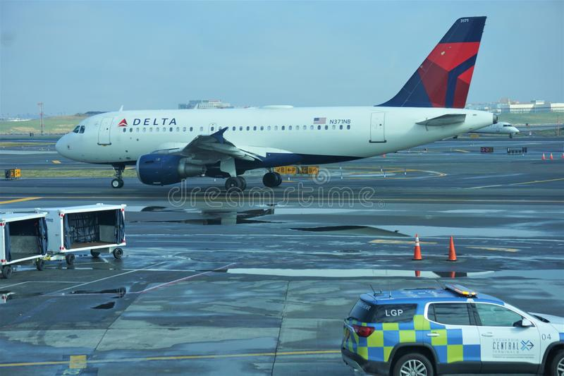 Vehicles on tarmac at LaGuardia Airport April 2019. Large cars Delta plane using the painted yellow traffic designs on the asphalt tarmac of the airport after a royalty free stock photography