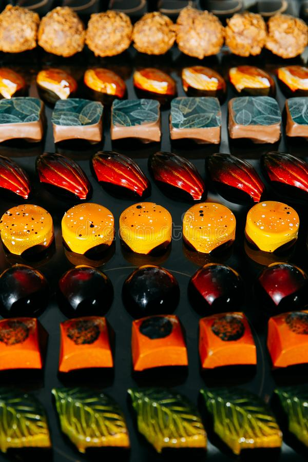 Large choice of handmade chocolates in rows royalty free stock photos