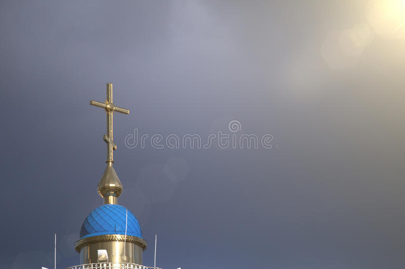 A large Christian cross on which falls a ray of sun through the clouds royalty free stock photos