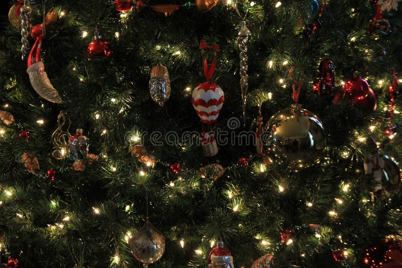 Large Christmas tree decorated with various ornaments, twinking lights throughout branches. Background image of Christmas tree decorated with various nostalgic stock photo