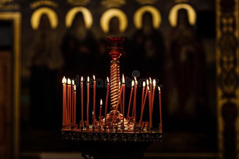 On a large Church copper candlestick lit a small candle. Orthodox Christian Church. Religion royalty free stock photography