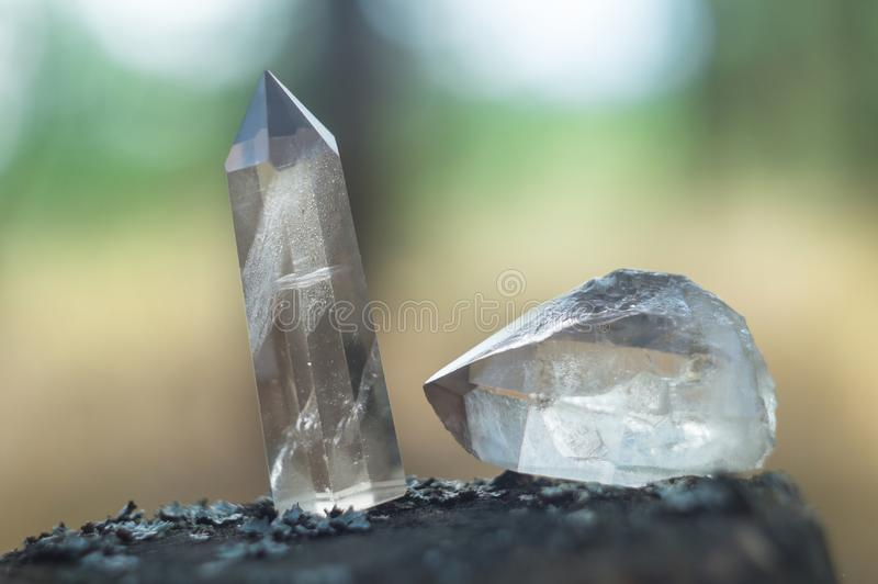 Large clear pure transparent great royal crystal of quartz chalcedony diamond brilliant on nature blurred bokeh background closeup. Large clear pure transparent stock image
