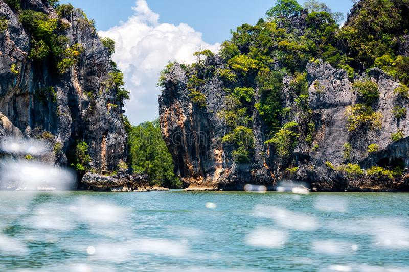 Large cliffs and mountains of islands in Phang Nga archipelago, splash of water from speed boat. View on large cliffs and mountains of islands in Phang Nga royalty free stock images