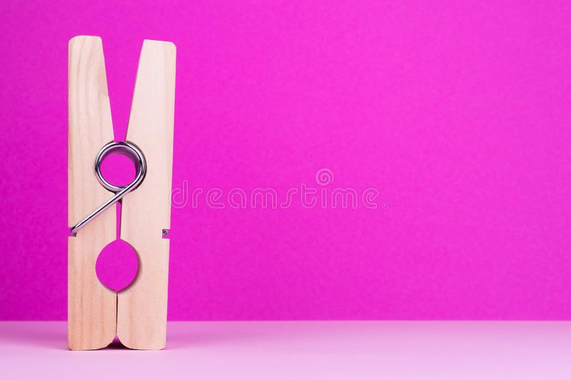 Large clothespin on pink background. Decorative clothespin, place for text stock photo