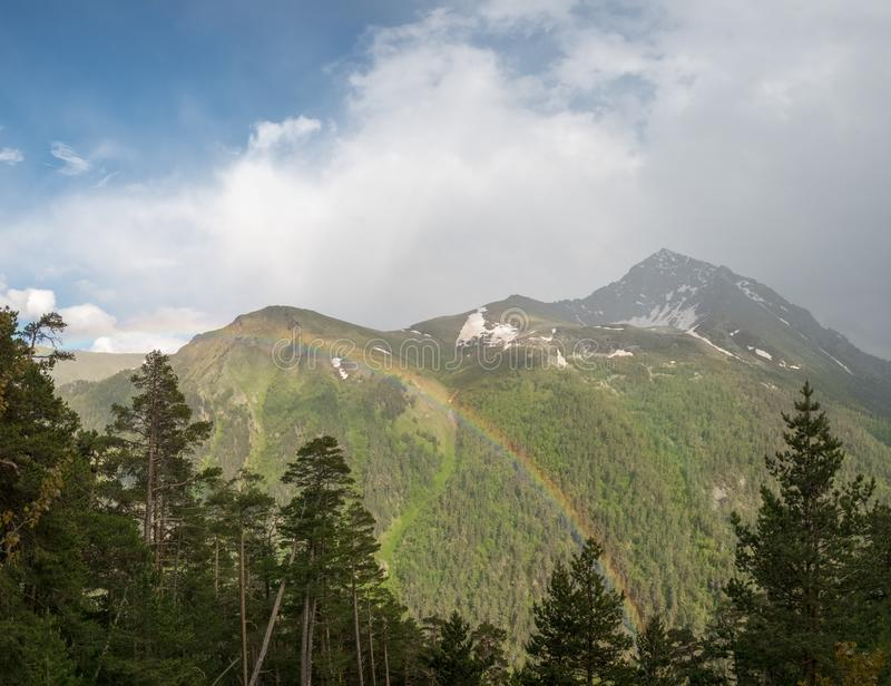 A large cloud and a rainbow over a mountain top with snow and green forested trees. And coniferous trees in the foreground stock image