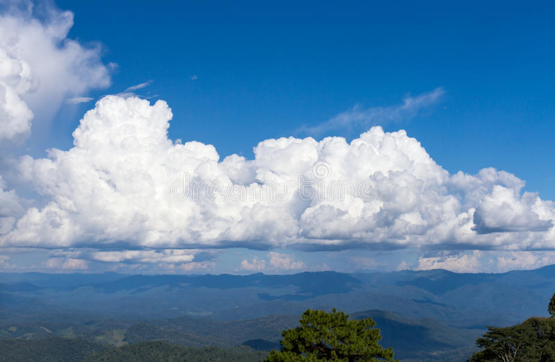 Large cloud sky. Large white cloud and blue sky over the forest mountains stock photos