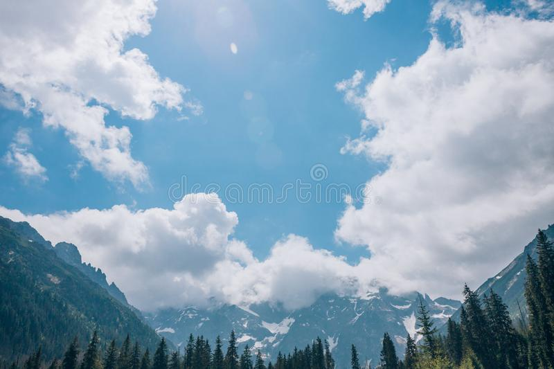 Large clouds over a mountain valley on a sunny summer day. Alps royalty free stock photos