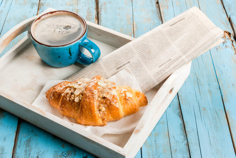 Large coffee mug, croissant and newspaper stock images