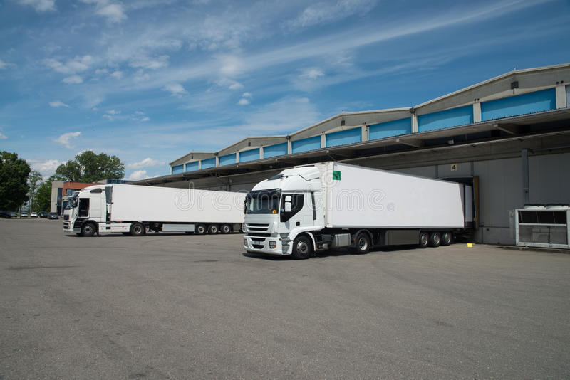 Large cold warehouse (Refrigerated trucks). Refrigerated trucks load and unload food in cold storage stock photo