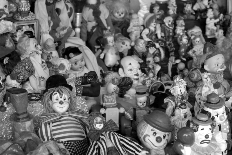 Large group of smiling and scary clowns in shop window, Austin, Texas, 2018. Large collection of grinning clowns that scare many people while delighting others stock photos
